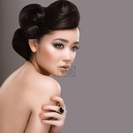 Beautiful girl with oriental type evening hair and makeup. Beauty face.