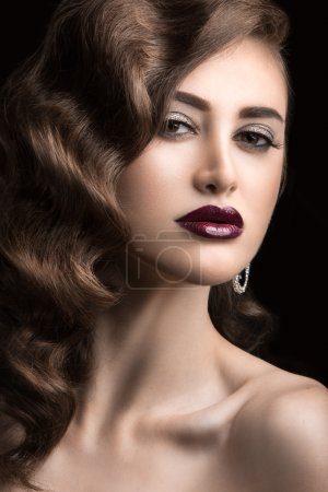 Beautiful woman with evening make-up, burgundy lips and curls. Beauty face.
