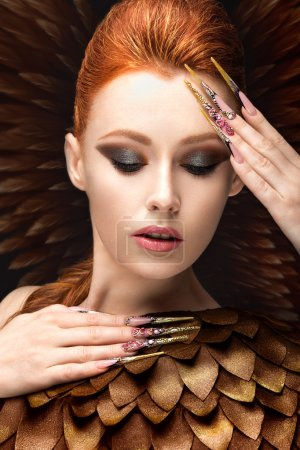Beautiful girl in the image of the Phoenix with bright makeup, long fingernails and red hair. Beauty face.