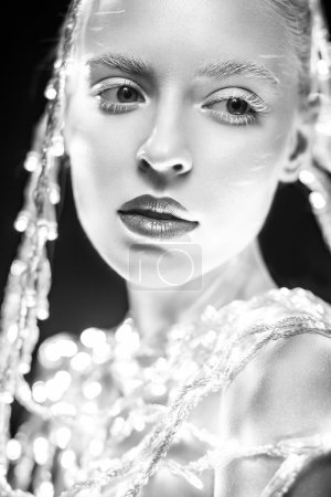 Pretty girl with glowing lanterns, white skin and makeup. Black and white photo.