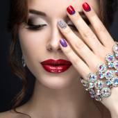 Krásná dívka s světlé večerní make-up a červená manikúra s kamínky. Nail design. Krása obličej