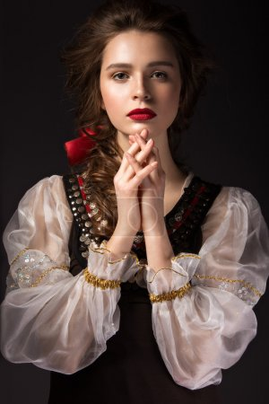Photo for Beautiful Russian girl in national dress with a braid hairstyle and red lips. Beauty face. Picture taken in the studio on a black background. - Royalty Free Image
