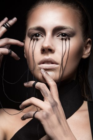Beautiful girl with creative make-up in Gothic style and the threads of eyes. Art beauty face.