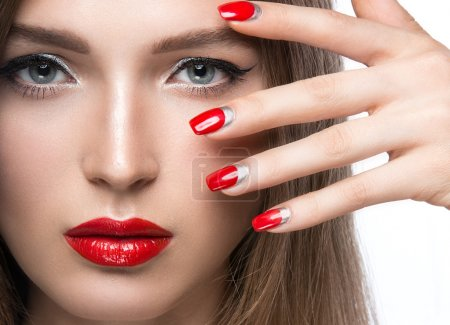Beautiful young girl with a bright make-up and red nails. Beauty face.