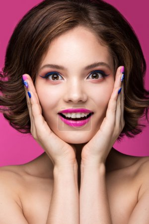 Beautiful model girl with bright pink makeup, smile and colored  nail polish. Beauty face. Short colorful nails