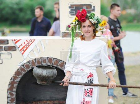 Photo pour Gomel, Belarus - 6 juillet: Every Jule nombreux biélorusses célébrent la fête appelée la nuit d'Ivan Kupala. Gomel, en Biélorussie. La jeune fille dans un costume national et le fourneau russe. - image libre de droit