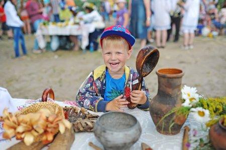 Photo pour Gomel, Belarus - 6 juillet: Every Jule nombreux biélorusses célébrent la fête appelée la nuit d'Ivan Kupala. Gomel, en Biélorussie. Le garçon heureux avec une grosse cuillère en bois. - image libre de droit