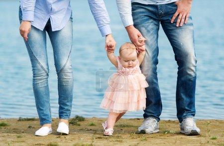 Photo pour Le père et la mère enseignent à la petite fille à faire les premiers pas indépendants . - image libre de droit