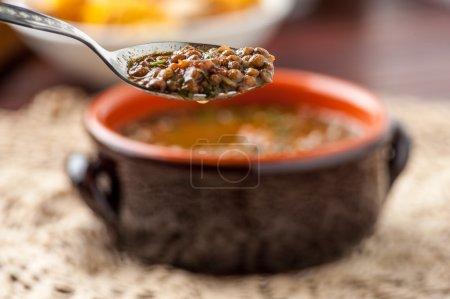 Photo pour Soupe de lentilles avec cuillère sur une table - image libre de droit