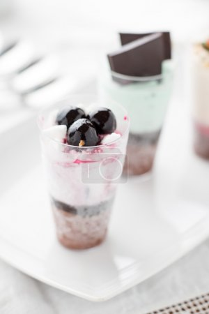 Photo for Ice cream in a glasses as dessert on white ceramic plate with blurred background - Royalty Free Image