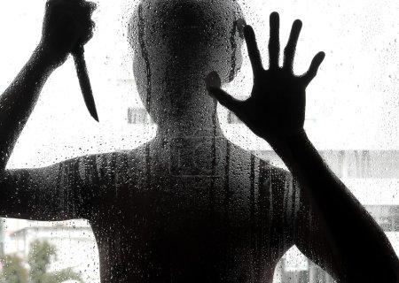 Schattenhafte Gestalt mit Messer hinter Glas