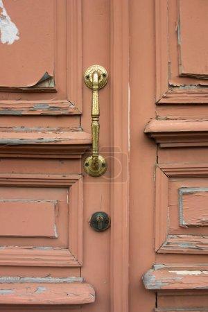 una vieja puerta torcida con un viejo mango dorado.