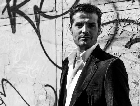 Handsome man portrait in the city near graffiti wall monochrome