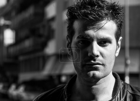 Handsome man portrait in the city shadows black and white