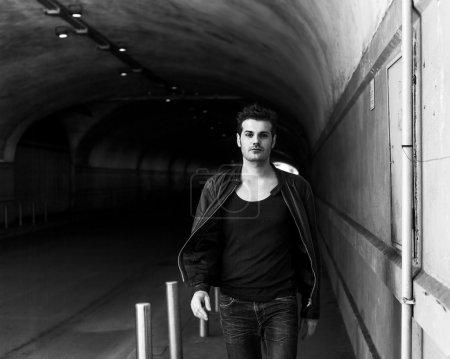 Handsome man portrait walking in underpass in the city monochrom