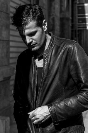 Man in the shadows wearing leather jacket and looking down