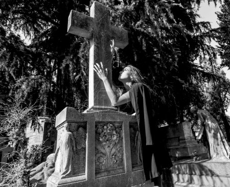 Woman in grief touching and looking at grave cross monochrome