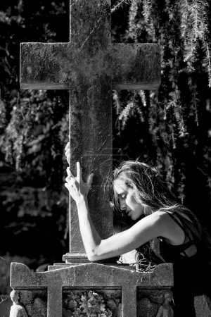 Woman portrait in grief enclosing grave cross monochrome
