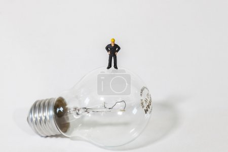 Tiny man standing on a light bulb on white background