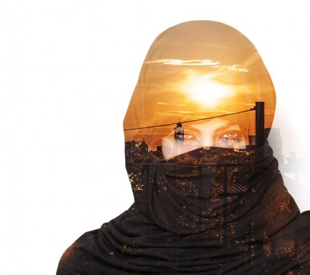 Double exposure of woman wearing burqa and cityscape at sunset