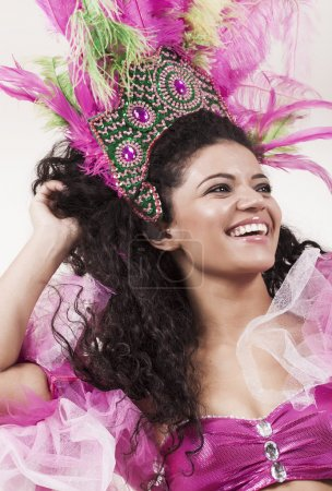 Happy and beautiful samba dancer wearing traditional pink costum