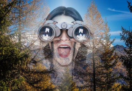 Double exposure of girl looking through binoculars and mountain