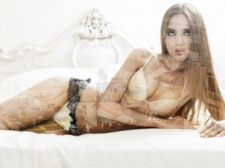 Double exposure of gorgeous girl on bed and cityscape
