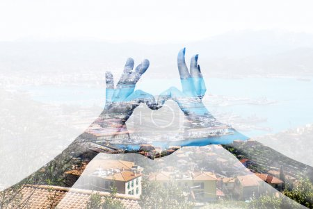 Double exposure of heart hand gesture and italian landscape