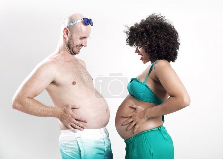 Beautiful and funny pregnant couple comparing bellies