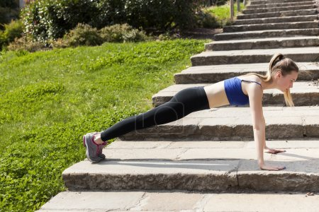Athletic woman doing push-ups in the city