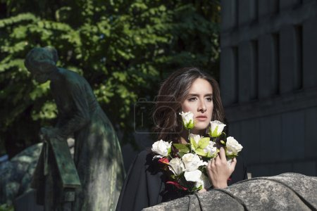 Sad woman portrait holding white roses near a grave