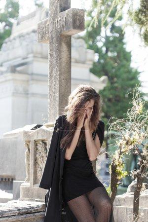 Sad woman portrait sitting near a grave