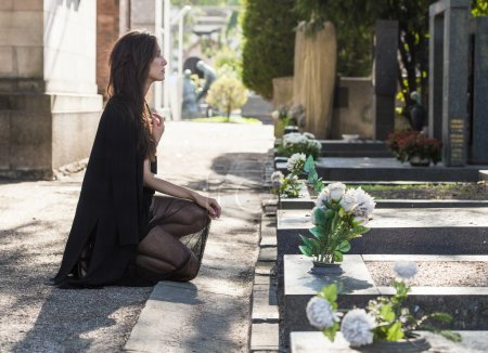 Woman portrait on her knees in front of a grave