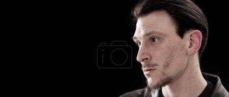 Handsome man portrait looking aside on black background letterbo