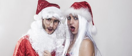 Girl wearing Christmas hat unmasking Santa Claus letterbox
