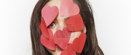 Girl with face covered with paper hearts letterbox