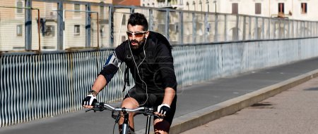 Sportsman riding bicycle in the city and wearing sunglasses lett