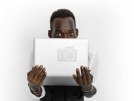 Businessman portrait hiding behind laptop