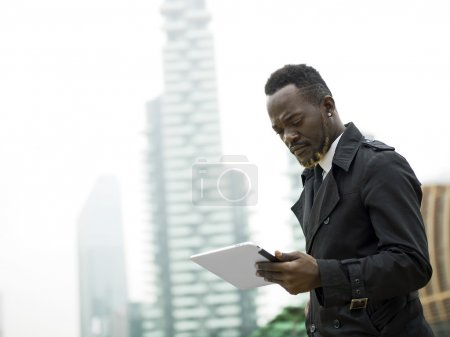 Businessman portrait in the city looking at tablet