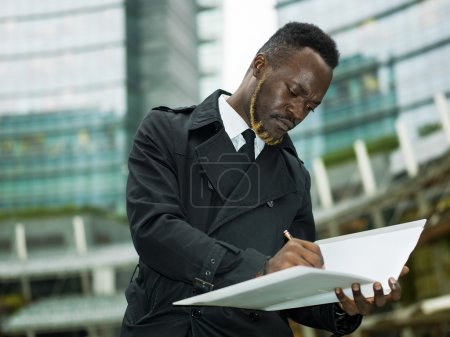 Businessman portrait in the city writing in folder