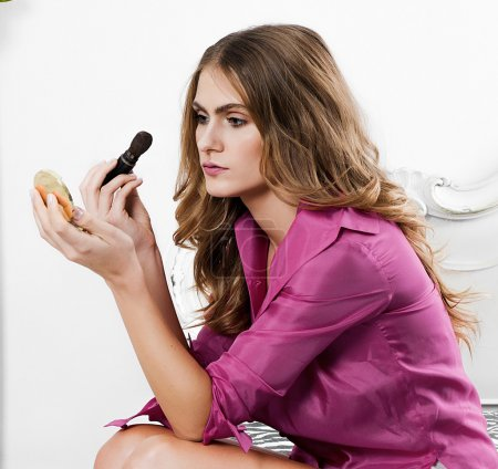 Woman portrait putting on makeup while sitting on bed closeup