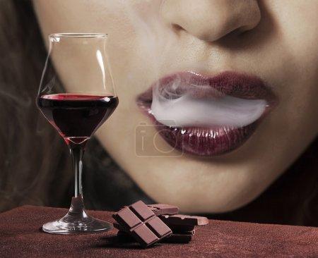 Photo pour Verre à vin rouge avec chocolat et bouche féminine fumant - image libre de droit