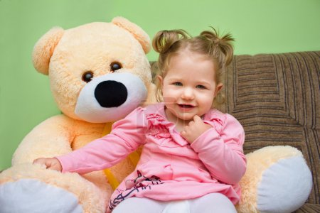 Little girl with big teddy bear sitting on sofa in the living roo