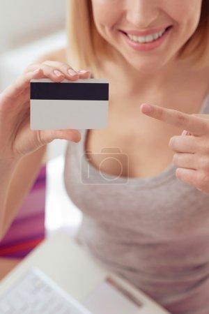 Photo pour L'argent est le pouvoir. Gros plan de femmes tenant une carte de débit et la pointant du doigt tout en souriant - image libre de droit
