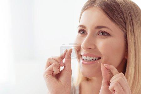 Photo pour Soins de beauté. Jeune jolie femme nettoie ses dents avec de la soie dentaire le matin - image libre de droit