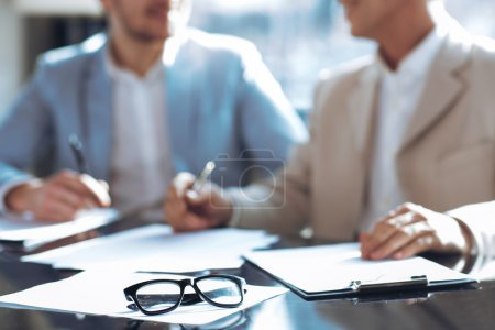 Photo for Involved in communication. Selective focus of glasses lying on the table with pleasant colleagues having discussing in the background - Royalty Free Image