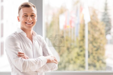 Positive man standing near window