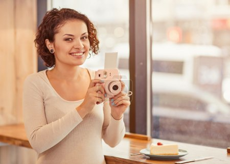 Smiling woman holding photo camera