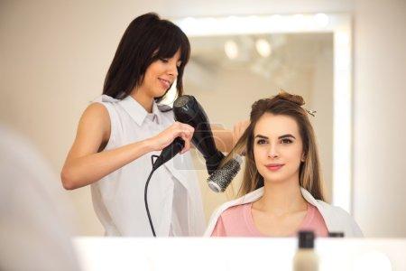 Photo pour Presque fini. Agréable coiffeur professionnel positif tenant sèche-cheveux et sèche-cheveux de sa cliente tout en travaillant dans le salon de coiffure - image libre de droit
