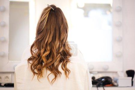 Photo pour Reste belle. Agréable femme bouclée assise dans le salon de coiffure - image libre de droit